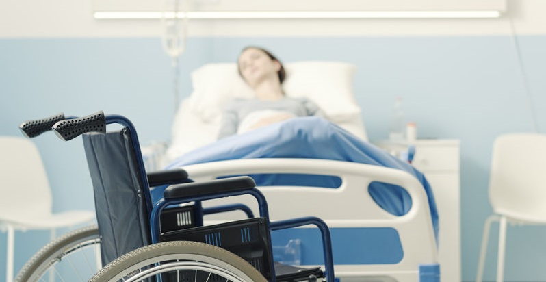 Person Lying in Hospital Bed Next to Wheelchair