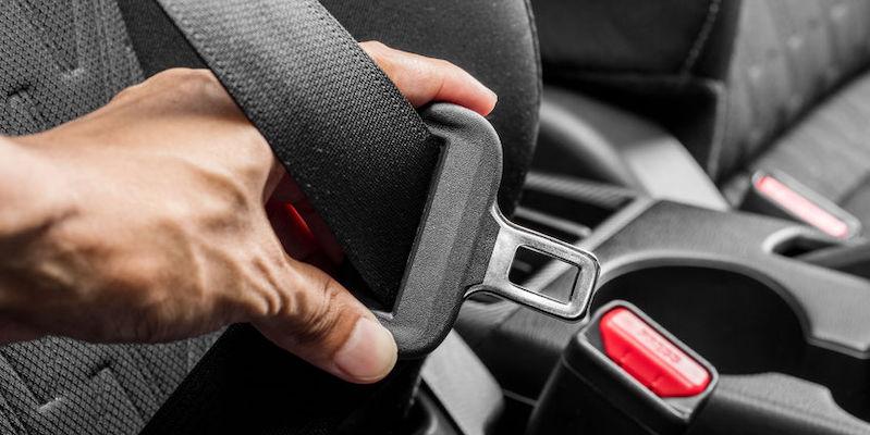 Close-up a hand buckling in a seat belt in a car.